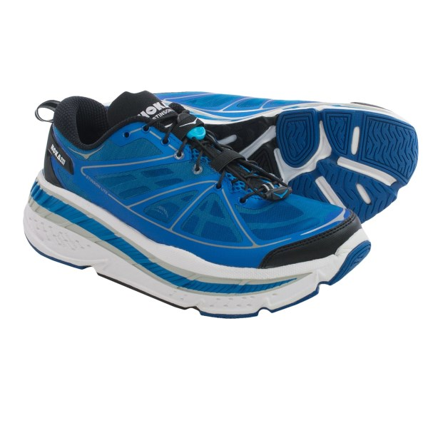 CLOSEOUTS . An update to the companyand#39;s most cushioned road design, Hoka One Oneand#39;s Stinson Lite running shoes offer improved durability and a lower profile tongue. It provides oversize cushioning for a pillow-soft landing and utilizes a Late-Stage Meta-Rocker midsole frame for enhanced forefoot support. Available Colors: GREY/LIME/RED, BLUE/WHITE/BLACK, BLACK/TRUE RED. Sizes: 7.5, 8, 8.5, 9, 9.5, 10, 10.5, 11, 11.5, 12, 12.5, 13, 13.5, 14, 7.